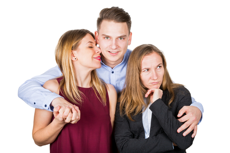 Picture of a happy couple and a frustrated ex girlfriend, posing on isolated background Stock Photo
