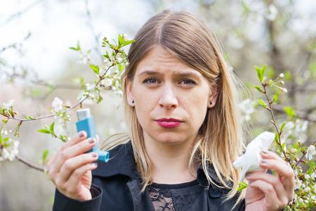 alergenos: Imagen de una mujer joven con alergia al polen, sosteniendo un broncodilatador al aire libre