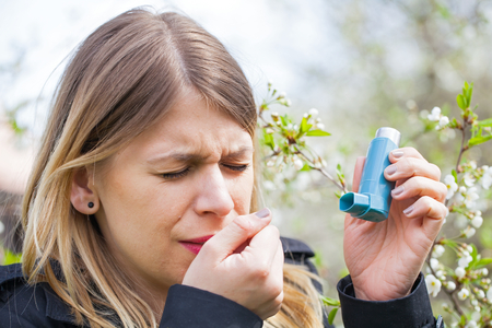 Picture of a young woman having pollen allergy, holding a bronchodilator outdoor Stock Photo