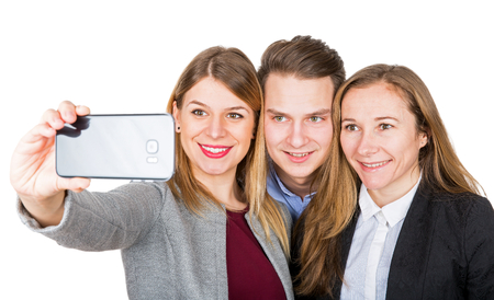 Picture of cheerful young people taking a selfie with a smartphone on isolated background