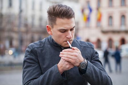 joven fumando: Imagen de un apuesto joven fumar un cigarrillo en la ciudad, al aire libre