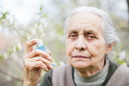 Close up picture of an elderly woman having an asthma attack, holding a bronchodilator