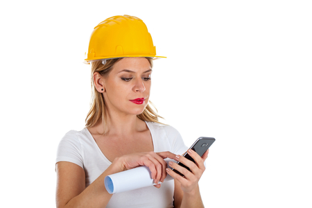 Picture of a young female constructor having a phone call, posing on isolated background