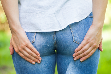 Close up picture of a young woman holding her butt, she needs to poop, outdoor