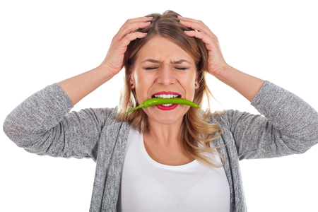 Picture of a beautiful woman with a chili paprika in her mouth, too spicy vegetable