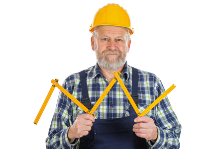 delineation: Picture of an elderly builder with construction instruments in his hands posing on isolated background Stock Photo