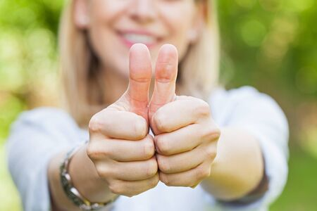 Close up picture of smiling woman showing thumbs up outdoor