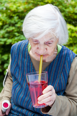 Portrait of an elderly woman with alzheimer disease drinking raspberry juice in the garden Stock Photo