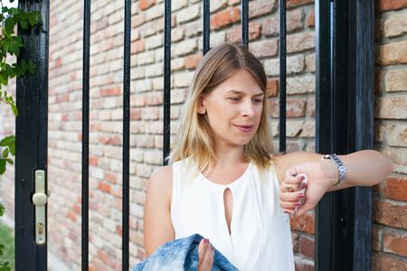 Picture of a smiling young woman opening the front door holding her denim jacket
