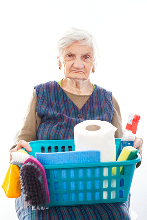 Portrait of a happy senior lady doing housework holding cleaning equipment