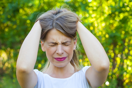 Picture of a very angry young woman having a breakdown  holding her head and hair outdoor