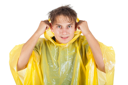 Picture of a caucasian young man wearing a yellow raincoat, posing on isolated background Stock Photo