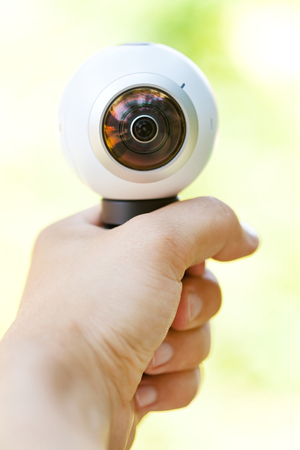 Close up picture of a 360 degree panoramic virtual tour camera in human hand outdoor Stock Photo