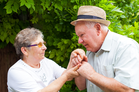 Senior man kissing his wifes hands, elderly couple in love outdoor
