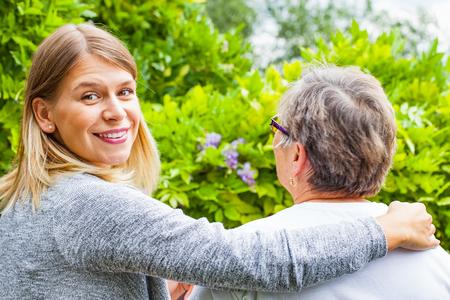 Afbeelding van een senior dame met haar vriendelijke verzorger in het park, achteraanzicht