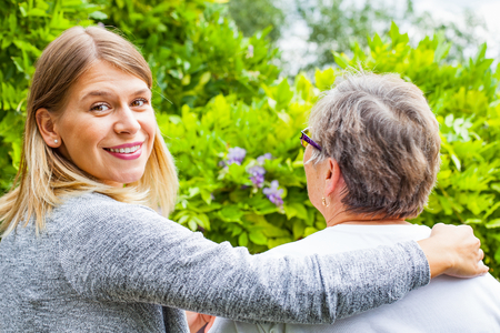 Picture of a senior lady with her friendly caregiver in the park, back view