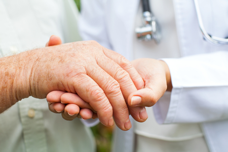 Close up young female doctor holding disabled elderly mans trembling hand Stock Photo