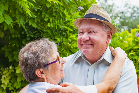 Cute elderly couple in love hugging and smiling outdoor in the green garden Stock Photo