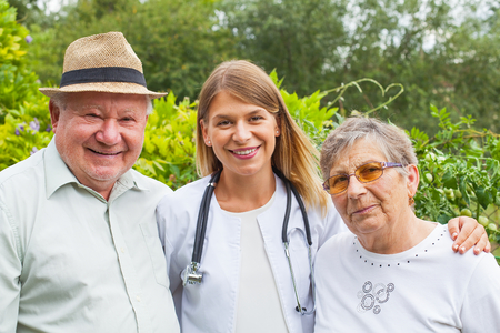 Friendly medical doctor with elderly couple smiling at the camera outdoor Standard-Bild