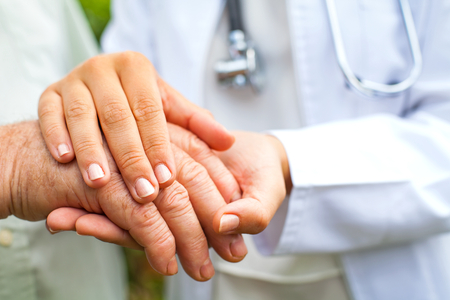 Close up young female doctor holding disabled elderly man's trembling hand