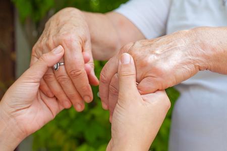 Sluit omhoog jonge verzorger die de trillende handen van het bejaarde wijfje, de ziekte van Parkinson houden
