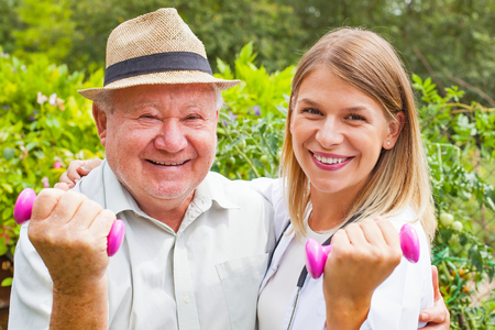 Smiling female therapist doing strength exercises with dumbbell with elderly male patient in the park