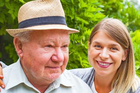 Glimlachende oudere man met mooie jonge kleindochter poseren in het park