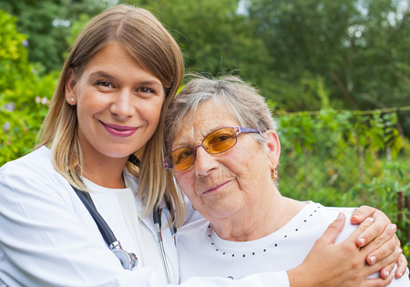 Disabled elderly woman in the park with young female medical doctor