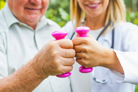 Close up female physician doing strength exercises with pink dumbbell with elderly man Stock Photo