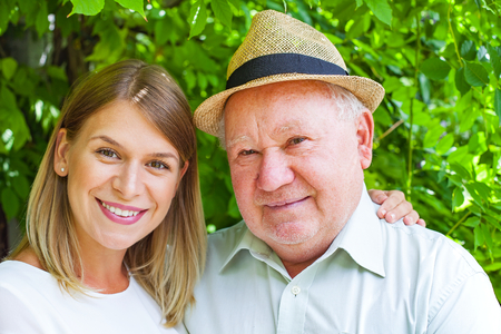 nurse hat: Smiling elderly man with beautiful young granddaughter posing in the park