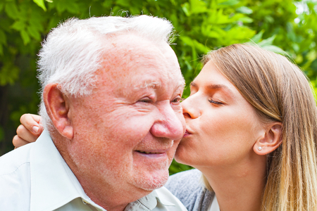 he: Young female giving a kiss to happy grandfather in he park