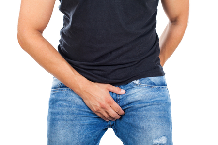 Close up young man with casual outfit holding his genitals on isolated background