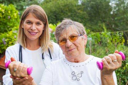 Oudere vrouw doet fitness oefeningen met domoren bijgestaan ??door lachende arts