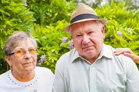 caregivers: Disabled senior couple and caregivers hands in the garden outdoor