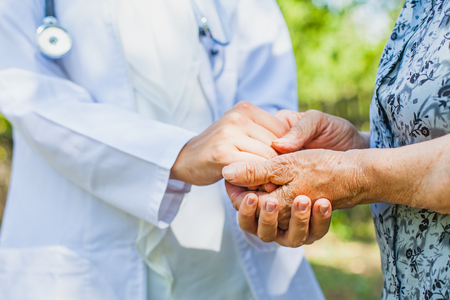 Close up medical doctor holding senior womans shaking hands, Parkinson disease