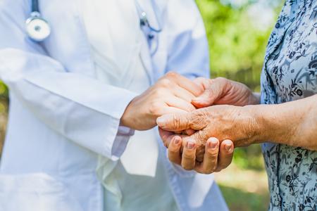 Close up medical doctor holding senior woman's shaking hands, Parkinson disease Standard-Bild