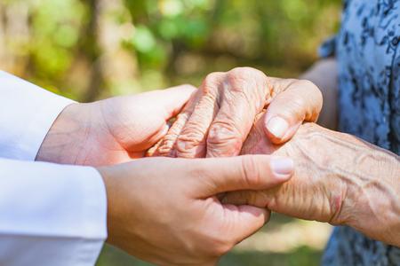 노인 여성의 떨리는 손을 잡고 의사를 닫습니다 스톡 콘텐츠