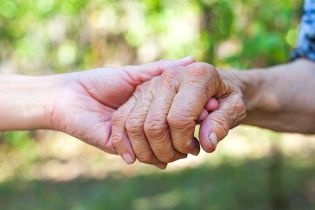 Close up elderly female's shaking hand held by young carer's hands outdoor Standard-Bild