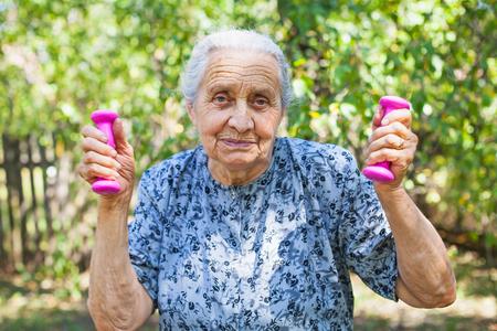 Vrolijk bejaarde die oefeningen met domoren doen openlucht op zomer. Lichamelijk herstel