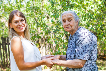 Disabled senior woman posing with friendly caregiver in the park Stock Photo