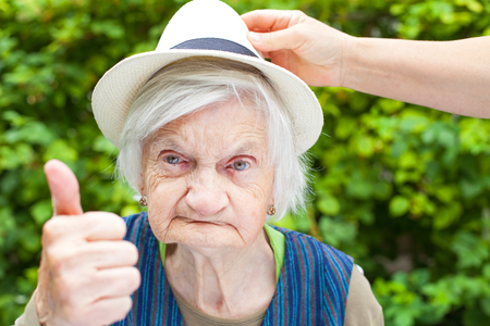 Elderly woman with mental disorder showing thumbs up in the park Stock Photo