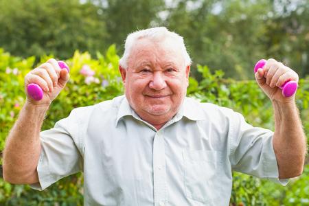 Bejaarde die geschiktheidsoefeningen met domoren in het park doet Stockfoto