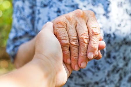 Close-up oudere vrouwelijke schudde hand gehouden door jonge carer's handen buiten