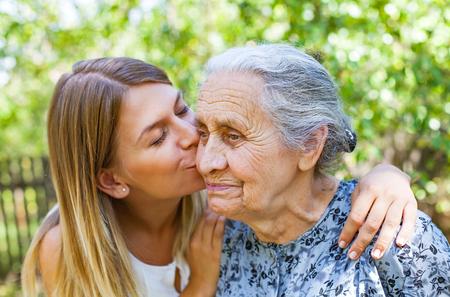 Jonge vrouw die haar oude grootmoeder in het park kust