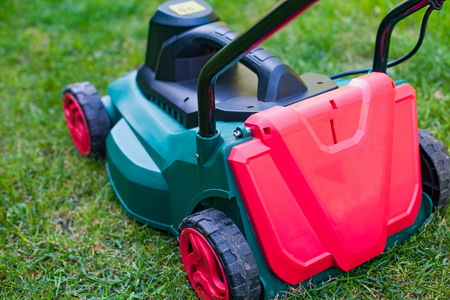 Close up modern lawn mower on the grass in the backyard Stock Photo