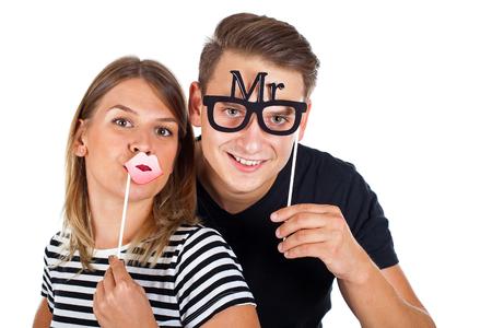 Beeld van een gelukkig paar poseren met photobooth accessoires op geïsoleerde achtergrond