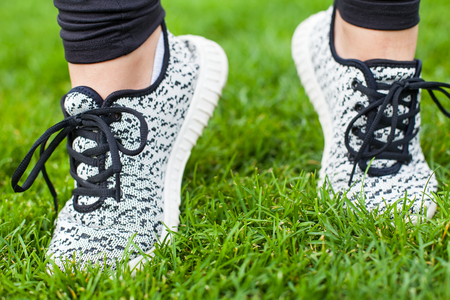 Close up sportive female training shoes on the green grass while doing fitness exercises