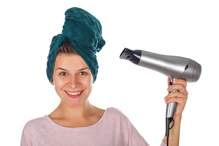 Smiling young woman with bath towel on head holding a hair dryer - isolated background