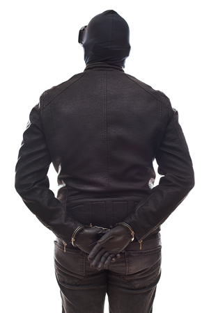 Back view dangerous criminal wearing black clothes and mask with handcuffs on isolated background Stock Photo