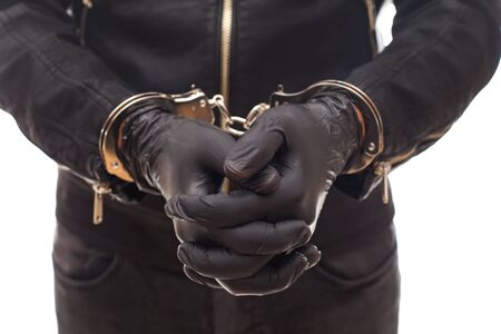Close up dangerous criminal hands with gloves handcuffed on isolated background